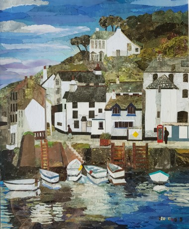 Polperro Harbour with white buildings and fishing boats on the sea