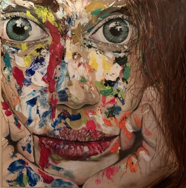 This is a contemporary image of a woman with an expressive face covered with coloured paint.